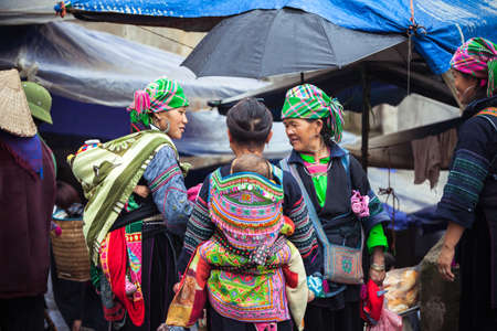 Sapa, Lao Cai, Vietnam - 6 May 2014: Hmong tribal women with baby in national clothes on the local market, Sapa, Northern Vietnam on 06 May 2014.
