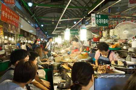 Сеул, Республика Корея - 14 августа 2014: Люди едят на продовольственных киосков в традиционном уличном рынке Gwangjang 14 августа 2014 года, Сеул, Южная Корея.