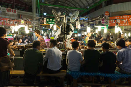 Seoul, Republic of Korea - 14 August 2014: People eating at the food stalls at the traditional Gwangjang street market on August 14, 2014, Seoul, Korea. Редакционное