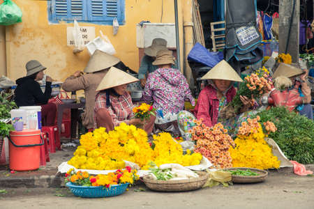 conical hat: Hoi An Vietnam March 14: Vietnamese women in conical hat selling flowers at the street market on March 14 2014 in Hoi An Vietnam.
