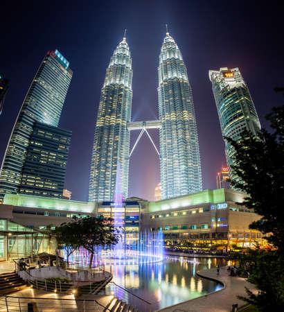 gemelas: Espect�culo de la fuente en la noche frente a las torres Petronas y Suria KLCC centro comercial de Kuala Lumpur Malasia.