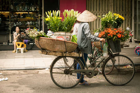 conical hat: Hanoi, Vietnam - May 12, 2014: Two women flower vendors in conical hat with bicycle having a conversation on the street of Old Quarter, Hanoi, Vietnam on May 12, 2014. Editorial