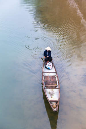 Vietnamese woman in conical hat floating on Perfume river, Hue, Vietnam.