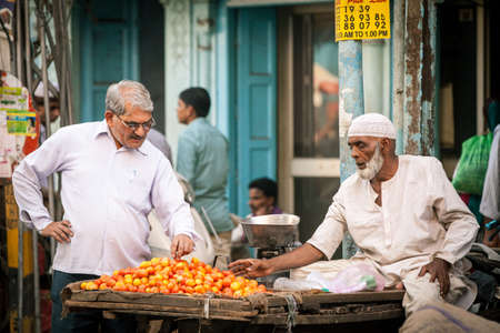 hard sell: Delhi, India - September 18, 2014: Indian man buying tomatoes from muslim vendor on the street of Old Delhi, India on September 18, 2014. Editorial