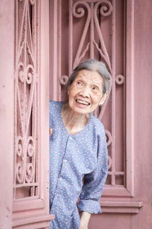 vietnamese ethnicity: Hanoi, Vietnam - April 26, 2014: Portrait of senior vietnamese woman looking out from the door on the street of Hanoi, Vietnam on April 26, 2014. Editorial
