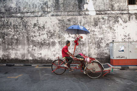 George Town,  Malaysia - March 21, 2016: Cycle rickshaw is riding down the street on March 21, 2016 in George Town, Penang, Malaysia. Stock Photo - 54608853