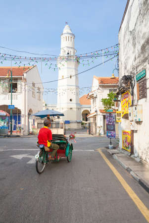 George Town,  Malaysia - March 21, 2016: Cycle rickshaw is riding down the street in front of the Lebuh Aceh Mosque. on March 21, 2016 in George Town, Penang, Malaysia. Stock Photo - 54608854
