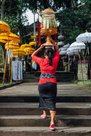 Balinese woman in traditional clothes  carrying ceremonial offerings on her head during Balinese New Year or Nyepi Day celebrations in Ubud, Bali. Stock Photo - 58639979