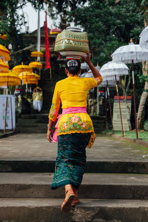 customs and celebrations: Balinese woman in traditional clothes  carrying ceremonial box with offerings on her head during Balinese New Year or Nyepi Day celebrations in Ubud, Bali. Stock Photo