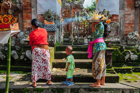 religious clothing: Ubud, Indonesia - March 01, 2016: Balinese women in traditional clothes making offerings in the temple, Ubud, Bali, Indonesia on March 01, 2016