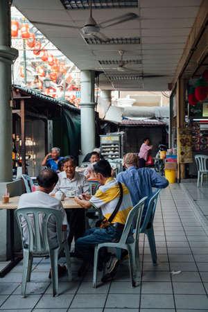 kopitiam: Kuala Lumpur, Malaysia - March 17, 2016:  Group of senior Chinese man having a breakfast in traditional Kopitiam, Chinatown, Kuala Lumpur, Malaysia on March 17, 2016.