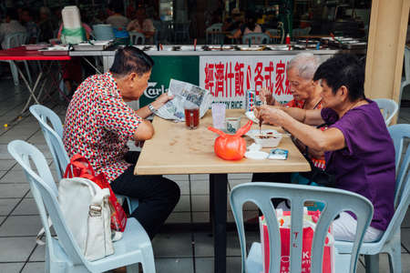 kopitiam: Kuala Lumpur, Malaysia - March 17, 2016:  Group of senior Chinese people having a breakfast in traditional Kopitiam, Chinatown, Kuala Lumpur, Malaysia on March 17, 2016.