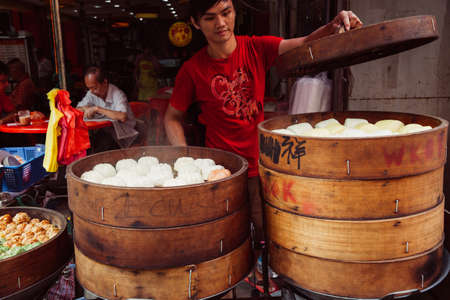march 17: Kuala Lumpur, Malaysia - March 17, 2016:  Young man cooking chinese traditional steamed buns at the street food stall in Chinatown, Kuala Lumpur, Malaysia on March 17, 2016. Editorial