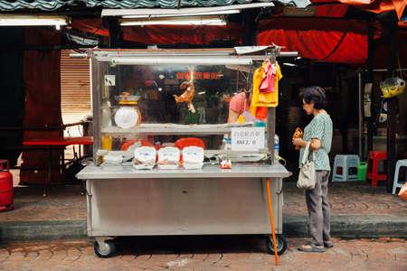 march 17: Kuala Lumpur, Malaysia - March 17, 2016:  Woman buying meat at the street stall in Chinatown, Kuala Lumpur, Malaysia on March 17, 2016.