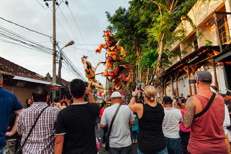 kuta: Kuta, Indonesia - March 08, 2016:  Tourists take photo of the Ogoh-ogoh statues at the parade on the eve of Nyepi day on March 08, 2016 in Kuta, Bali, Indonesia