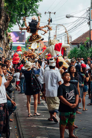 kuta: Kuta, Indonesia - March 08, 2016:  Visitors watch and take photo of the Ogoh-ogoh statues at the parade on the eve of Nyepi day on March 08, 2016 in Kuta, Bali, Indonesia Editorial