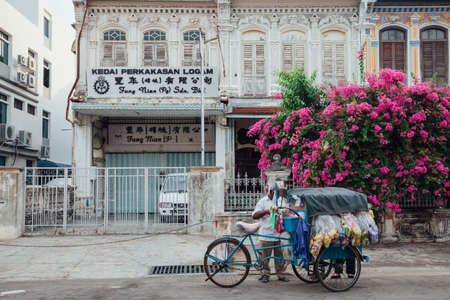 George Town,  Malaysia - March 22, 2016: Vendor sells snacks from the tricycle in UNESCO Heritage buffer zone in George Town, Penang, Malaysia on March 22, 2016. Stock Photo - 59370895