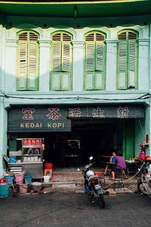George Town, Maleisië - 24 maart, 2016: De vrouw zit bij de lijst in de traditionele kopitiamkoffie in Chinatown, George Town, Penang, Maleisië op 24 Maart, 2016. Redactioneel