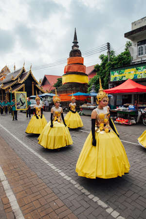 Chiang Mai, Thailand - August 24, 2016: Young girls in festival costumes parade near the ancient temple on August 24, 2016 in Chiang Mai, Thailand.