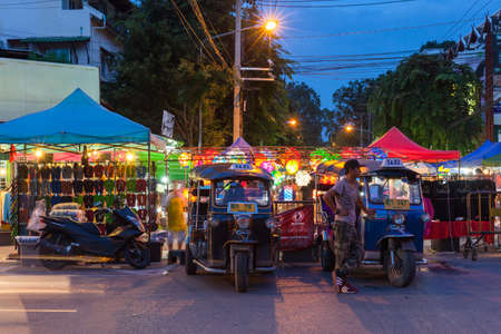 Chiang Mai, Thailand - August 21, 2016: Tuk-tuk taxis wait for customers near Saturday Night Market on August 21, 2016 in Chiang Mai, Thailand.