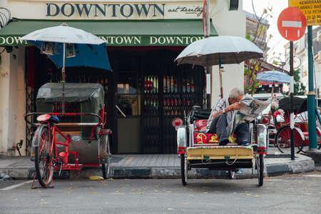 Джордж Таун, Малайзия - 21 марта 2016 года: Рикша читает газету, сидящую на трехколесном велосипеде на улице Джорджтауна, Пенанг, Малайзия 21 марта 2016 года.