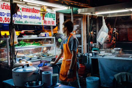 Chiang Mai, Thailand - August 27, 2016:  Food vendor waits for customers at the Saturday Night Market on August 27, 2016 in Chiang Mai, Thailand.