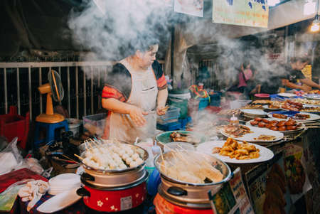 Chiang Mai, Thailand - August 27, 2016:  Thai woman cooks food for sale at the Saturday Night Market on August 27, 2016 in Chiang Mai, Thailand.