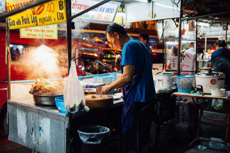 Chiang Mai, Thailand - August 27, 2016:  Man cooking food at the Saturday Night Market on August 27, 2016 in Chiang Mai, Thailand.