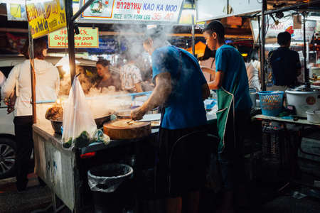 Chiang Mai, Thailand - August 27, 2016:  Father and sun cooking food at the Saturday Night Market on August 27, 2016 in Chiang Mai, Thailand. Редакционное