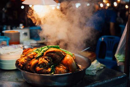 Горячая свинина остывает на ночном рынке в субботу вечером в Чиангмае, Таиланд. Фото со стока