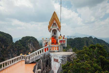 Краби, Таиланд - 10 апреля, 2016: Начинающие монахи наблюдают вершине холма Храма Тигра пещера горы 10 апреля 2016 года в городе Краби, Таиланд. Редакционное