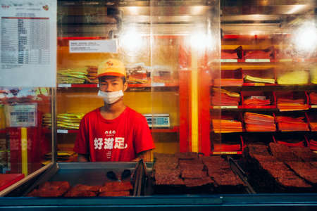 Куала-Лумпур, Малайзия - 17 марта 2016 года. Молодой человек продает китайское сухое мясо (Bakkwa) на продовольственном ларьке в Чайна-тауне, Куала-Лумпур, Малайзия 17 марта 2016 года.