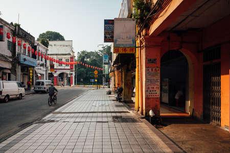 Kuala Lumpur, Malaysia - March 17, 2016: Man riding a bicycle down the street of Chinatown, Kuala Lumpur, Malaysia on March 17, 2016. Редакционное
