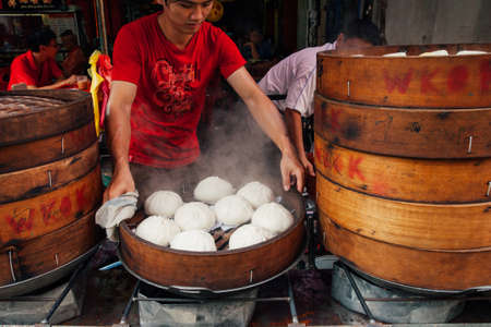 Kuala Lumpur, Malaysia - March 17, 2016:  Young man cooking chinese traditional steamed buns at the street food stall in Chinatown, Kuala Lumpur, Malaysia on March 17, 2016. Редакционное