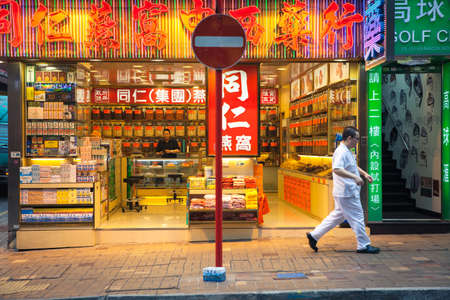 Hong Kong, China - February 16, 2014: Man passes by neon-lighted traditional Chinese medicine store on February 16, 2014 in Hong Kong, China. Редакционное
