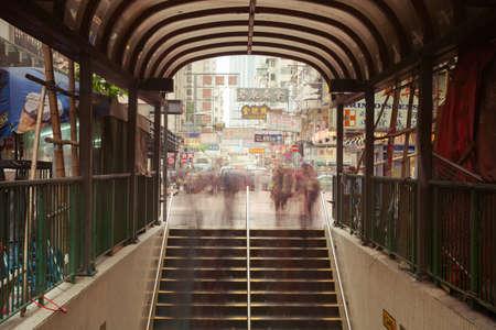 bajando escaleras: Hong Kong, China - 18 de febrero 2014: Movimiento enmascarado de gente que va por las escaleras del cruce subterráneo el 18 de febrero de 2014 en Kowloon, Hong Kong.
