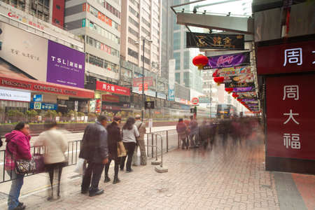 Hong Kong, China - February 18, 2014: People waiting for the bus at the bus stop in Kowloon district on February 18, 2014 in Hong Kong, China.