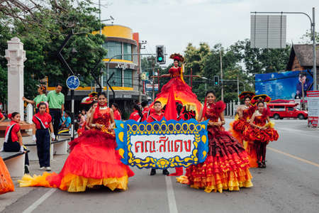 Chiang Mai, Thailand - August 24, 2016: Young girls and boys in festival costumes parade near the Three Kings Monument on August 24, 2016 in Chiang Mai, Thailand.