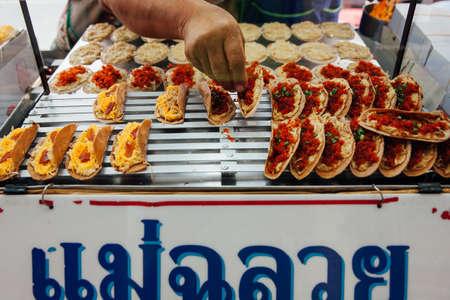 Bangkok, Thailand - September 11, 2016: Street vendor selling Khanom bueang (Thai Crepe) on September 11, 2016 in Bangkok, Thailand Редакционное