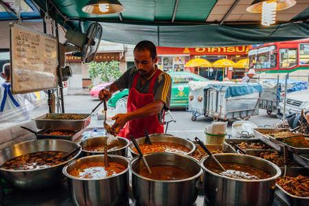 Бангкок, Таиланд - 11 сентября 2016 года: уличный торговец заливает карри в пластиковый пакет 11 сентября 2016 года в Бангкоке, Таиланд