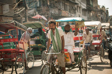 Delhi, India - September 18, 2014: Cycle rickshaw riding the vehicle under the heat on the street of Old Delhi, India on September 18, 2014.