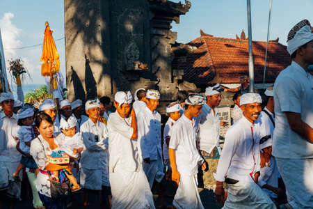 Bali, Indonesia - March 07, 2016: Balinese people in traditional clothes take part in the ceremonial procession during Balinese New Year celebrations.