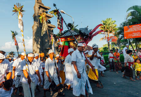 Bali, Indonesia - March 07, 2016: Balinese people in traditional clothes carry jempana or wooden litter at the procession during Balinese New Year celebrations. Stock Photo - 83118864