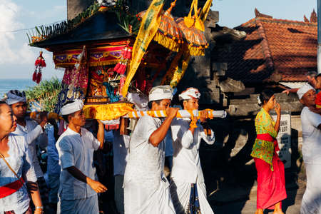 Bali, Indonesia - March 07, 2016: Balinese people in traditional clothes carry jempana or wooden litter at the procession during Balinese New Year celebrations.