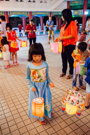 Kuala Lumpur, Malaysia - September 15, 2016:  Little girl plays with paper lanterns at Thean Hou Temple at the lantern parade during Mid-Autumn festival on September 15, 2016 in Kuala Lumpur, Malaysia. Редакционное