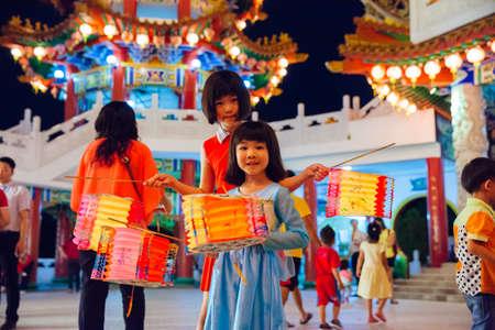 Куала-Лумпур, Малайзия - 15 сентября 2016 года. Маленькие девочки позируют с бумажными фонарями в храме Thean Hou Temple на параде фонарей во время фестиваля середины осени 15 сентября 2016 года в Куала-Лумпуре, Малайзия.