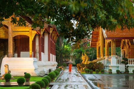 Монах шел под зонтиком в храме Ват Пхра Сингх, Чианг Май, Таиланд. Самый почитаемый храм Чианг Мая