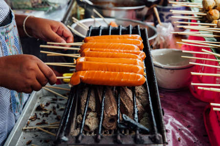 A street vendor makes grilled Thai sausages on skewers at the Warorot Market, Chiang Mai, Thailand.