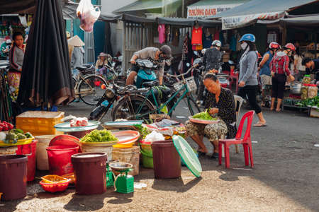 Nha Trang, Vietnam - July 14, 2016: Vietnamese woman sells vegetables at the morning market in Nha Trang, Vietnam on July 14, 2016.