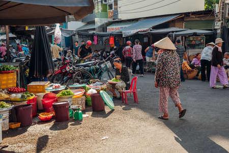 Нячанг, Вьетнам - 14 июля 2016 года: Вьетнамская женщина в конической шляпе выходит на утренний рынок в Нячанге, Вьетнам 14 июля 2016 года.